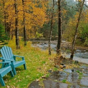 fall scenery with chairs by the river